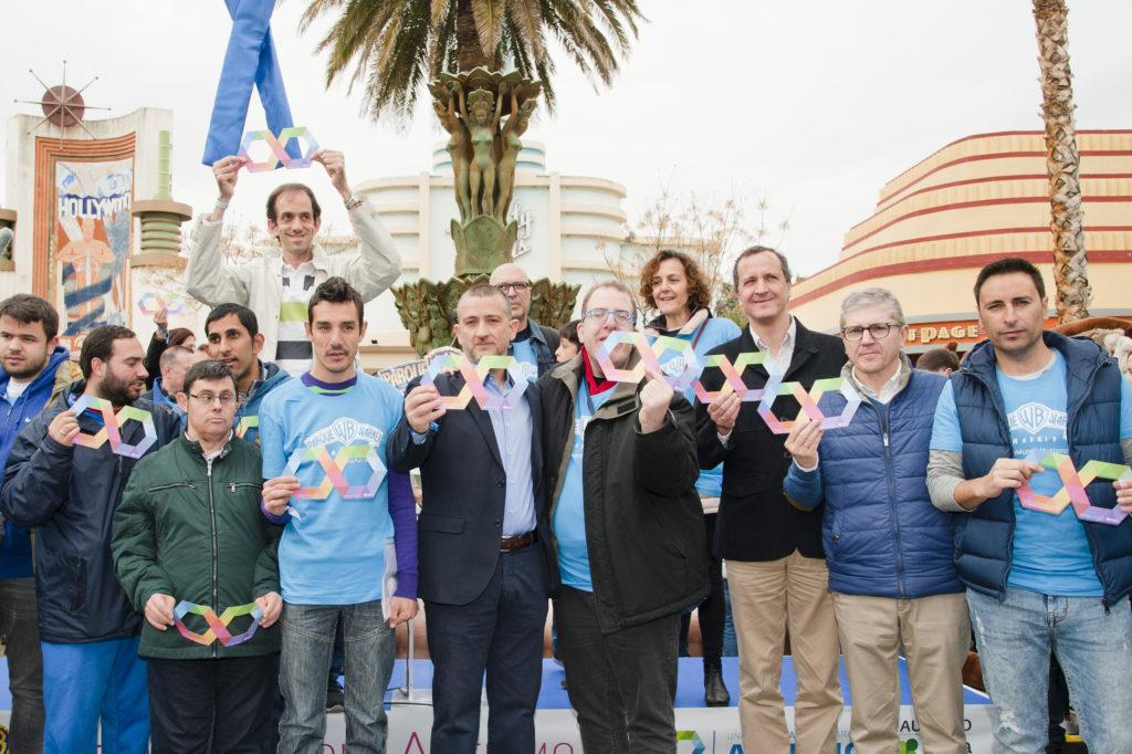 """Miembros del reparto de la película """"Campeones"""" y directivos de Parque Warner sujetando el símbolo del Autismo."""